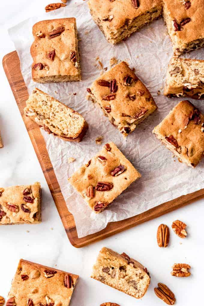 Maple pecan blondies cut into squares and arranged haphazardly on white parchment paper.