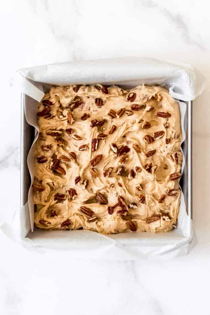 Maple pecan blondie batter in a square baking dish lined with parchment paper and chopped pecans sprinkled on top.
