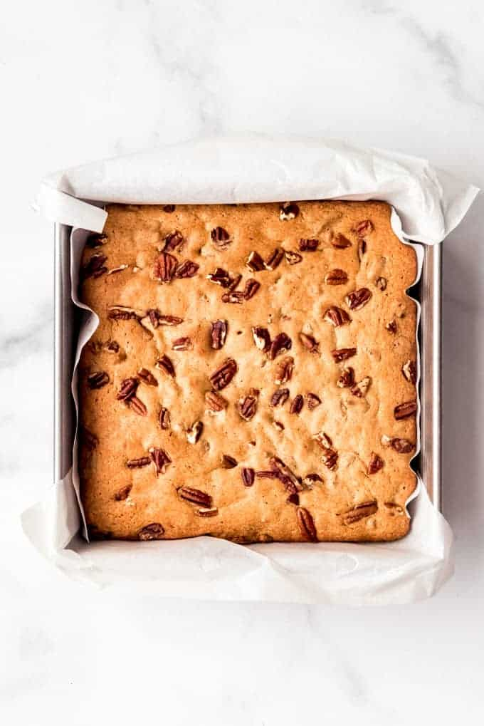 A square baking pan filled with blondies topped with pecans.