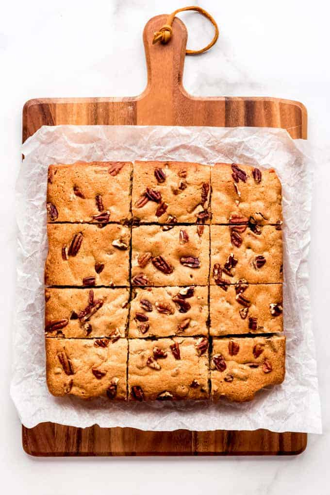 Blondies cut into 12 squares topped with chopped pecans on a cutting board.