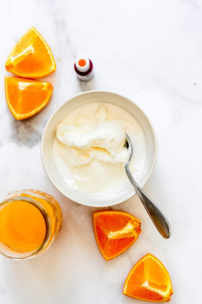 An white bowl filled with sherbet base next to orange juice and oranges.