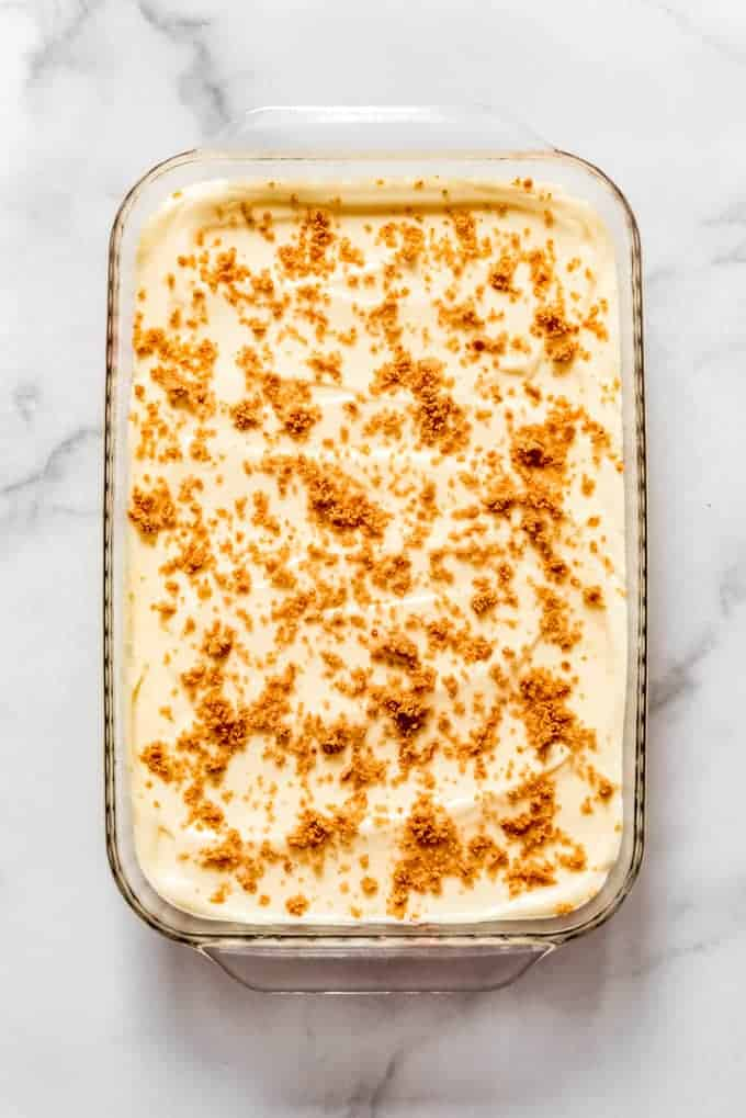 A large glass baking dish of pudding dessert with graham cracker crumbs sprinkled on top.