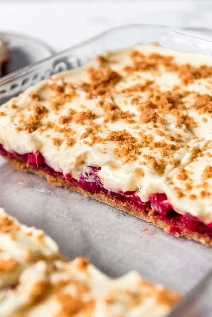 A side view of the layers of graham cracker crust, rhubarb filling and pudding topping in a layered dessert.