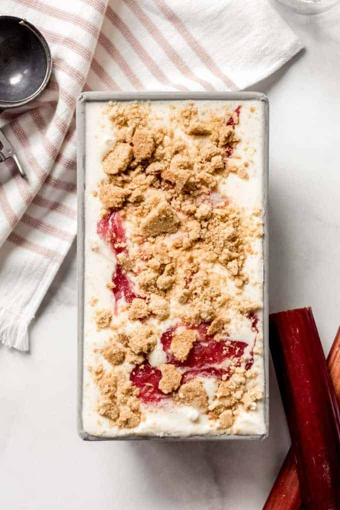 A metal bread pan filled with rhubarb crumble ice cream next to some stalks of rhubarb.