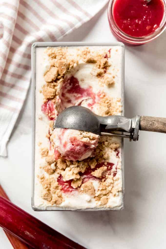 An ice cream scoop being used to scoop homemade rhubarb crumble ice cream.