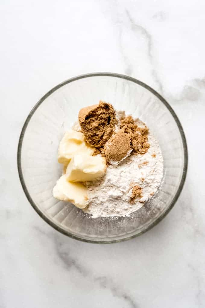 A glass bowl with brown sugar, flour, and butter.