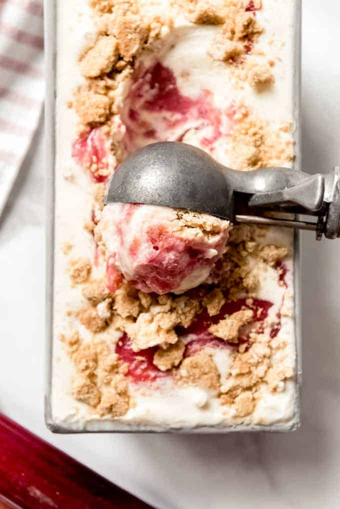 an ice cream scoopeer scoopign up a big ball of rhubarb crumble ice cream