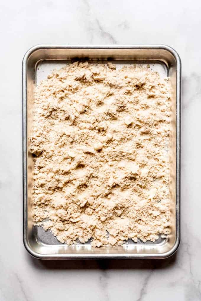 A baking sheet with crumble topping spread out on it to bake.