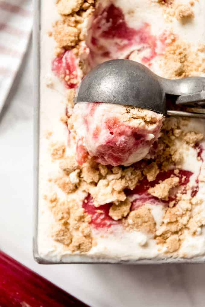 A close-up image of an ice cream scoop scooping a ball of rhubarb crumble ice cream.