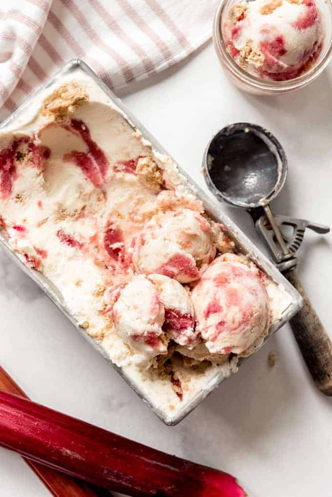 A bread pan filled with rhubarb crumble ice cream next to an ice cream scoop and stalks of rhubarb.