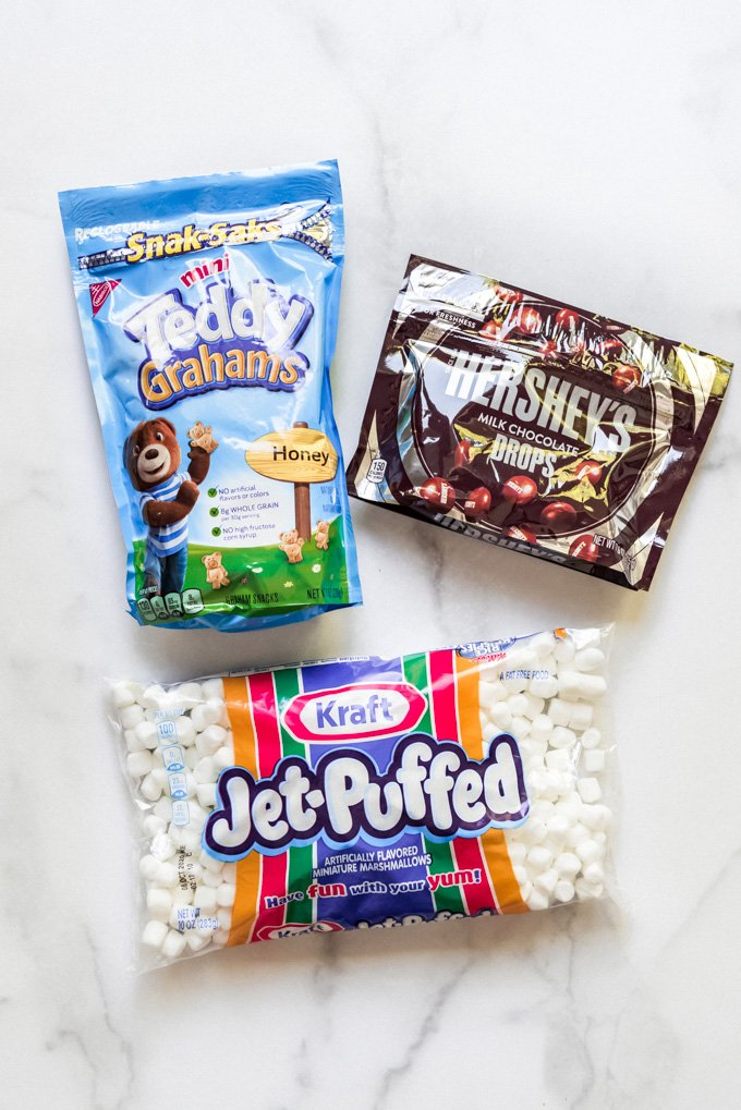 Packages of mini Teddy Grahams, Hershey's milk chocolate drops, and Kraft Jet-Puffed marshmallows on a white marble surface.