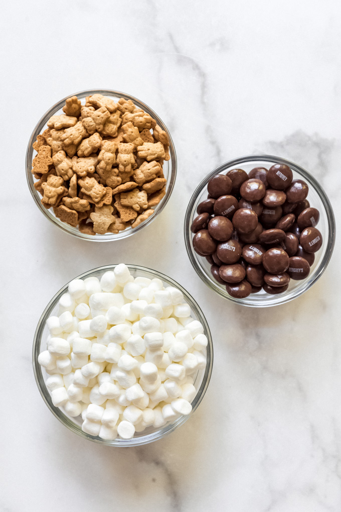 Teddy grahams, Hershey's chocolate drops, and mini marshmallows in three individual bowls on a white marble surface.