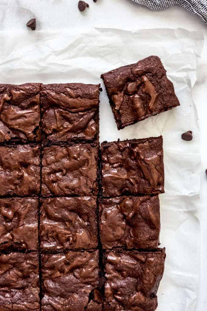 Brownies from scratch sliced into squares on a piece of parchment paper.
