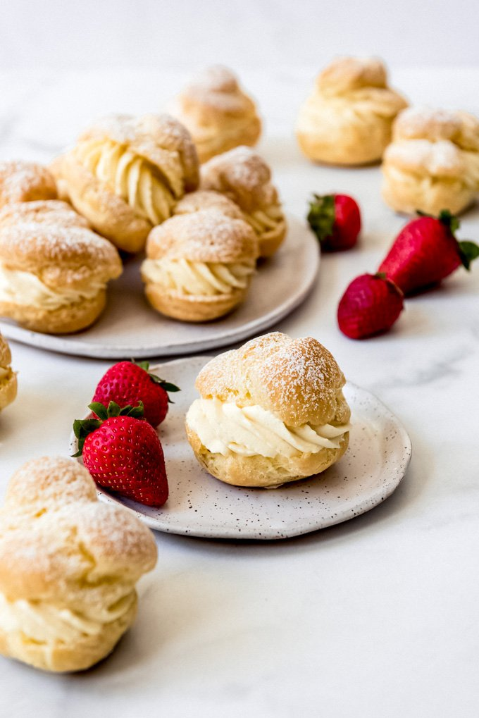 A cream puff on a plate with two strawberries next to more cream puffs.