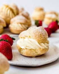 A cream puff filled with pastry cream on a plate with strawberries.