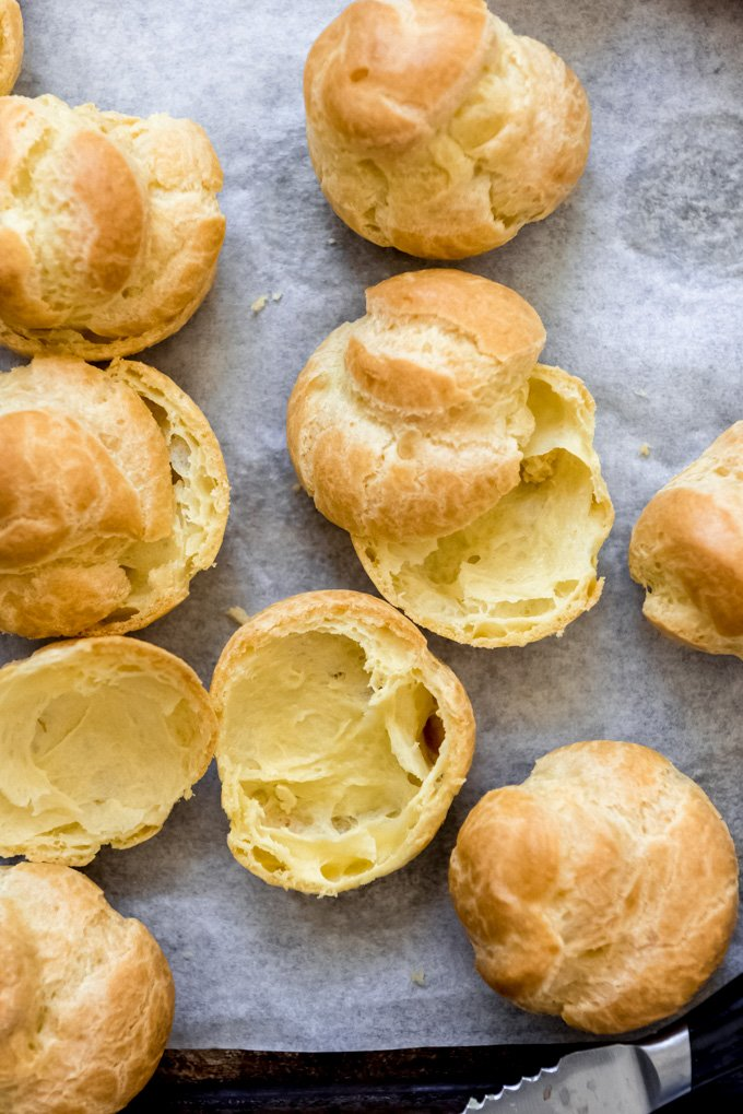 Homemade cream puffs that have been sliced open.
