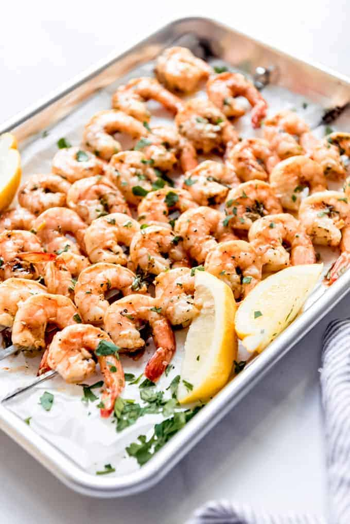 grilled shrimp skewers on parchment paper and baking tray, with lemon wedges