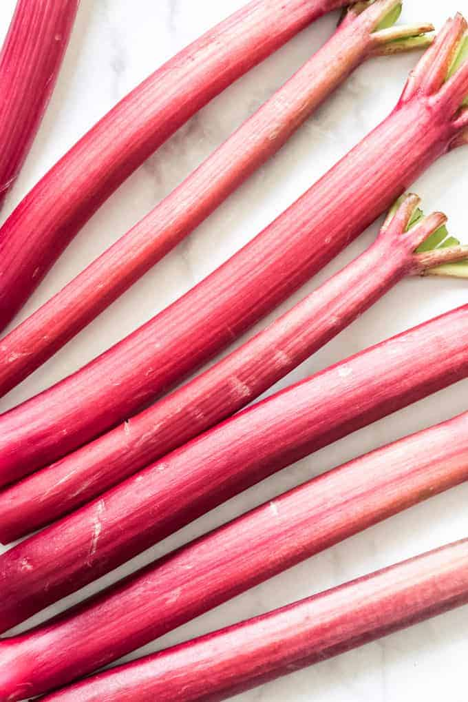 Bright pink rhubarb stalks lined up next to each other.