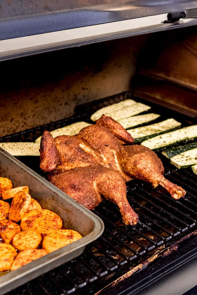 A spatchcock chicken on a Traeger pellet grill with zucchini and sweet potatoes.