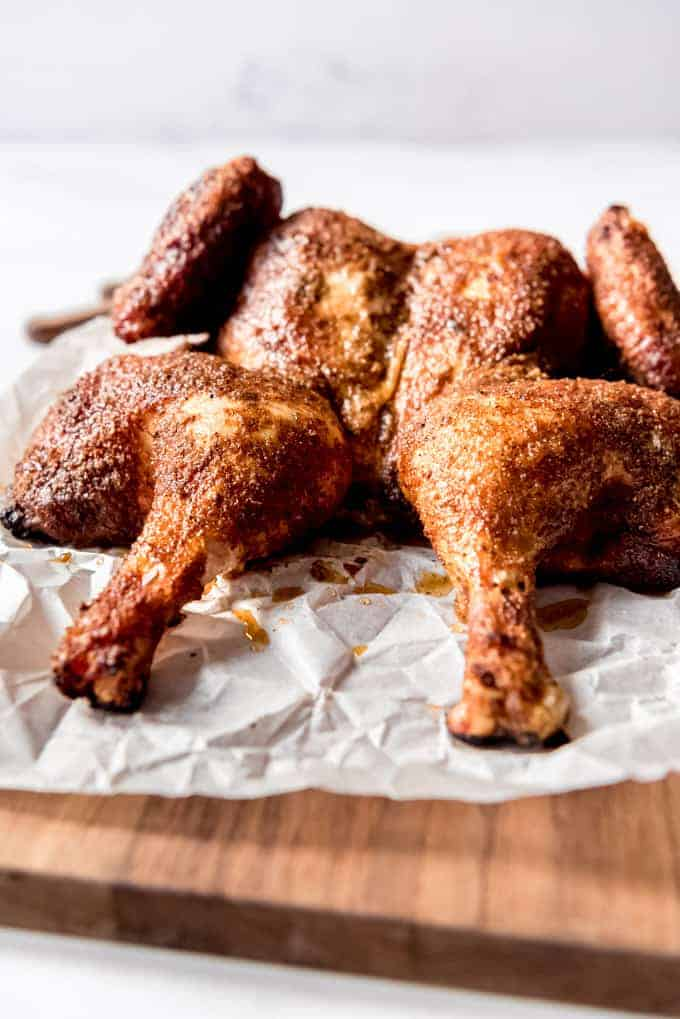 A spatchcock smoked chicken resting on parchment paper.