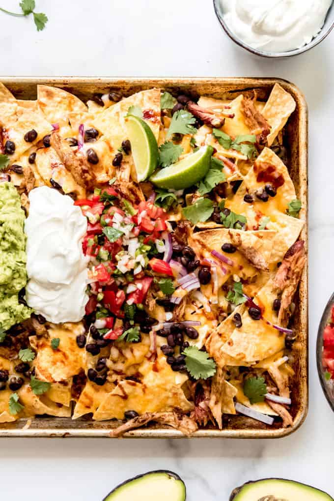 A baking sheet full of pulled pork nachos topped with pico de gallo, sour cream, and lime wedges.