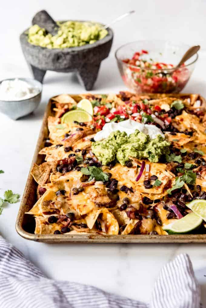 A baking sheet filled with nachos in front of bowls of sour cream, guacamole, and pico de gallo.