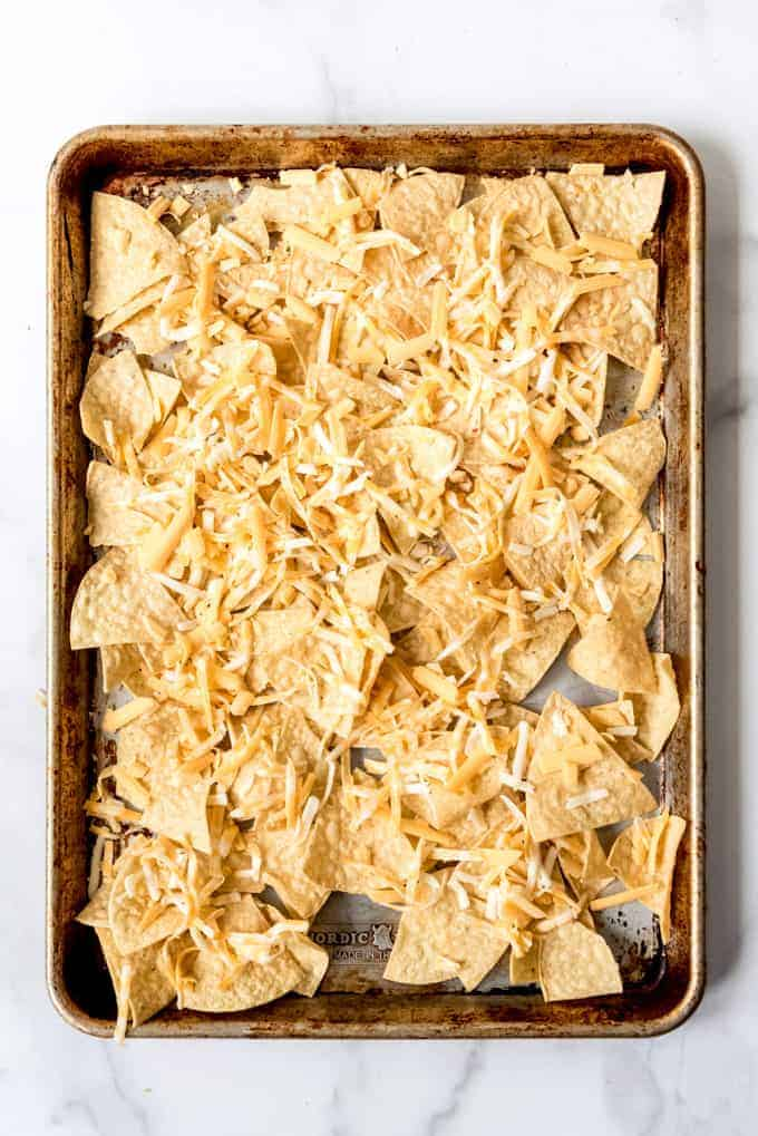 Cheese topped tortilla chips on a baking sheet