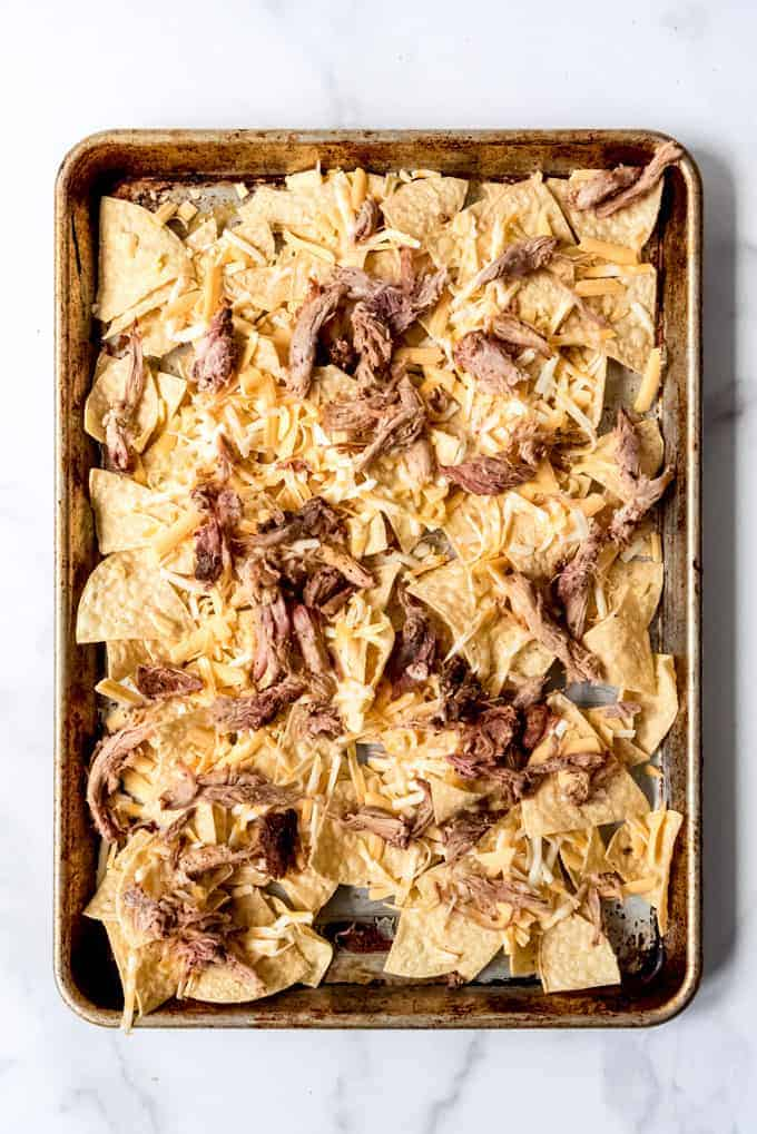 Pulled pork on cheese topped tortilla chips on a baking sheet
