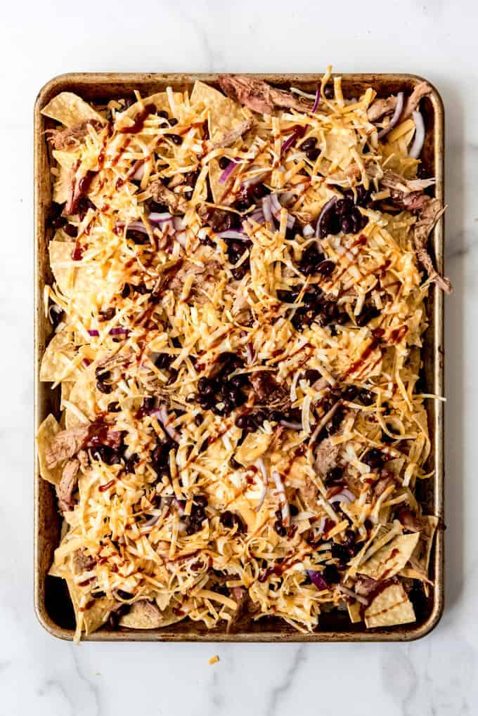 bbq pulled pork nachos on a baking sheet