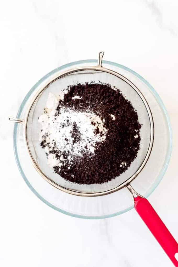 Almond flour, crushed Oreos, and powdered sugar being sifted through a fine mesh sieve into a glass bowl.