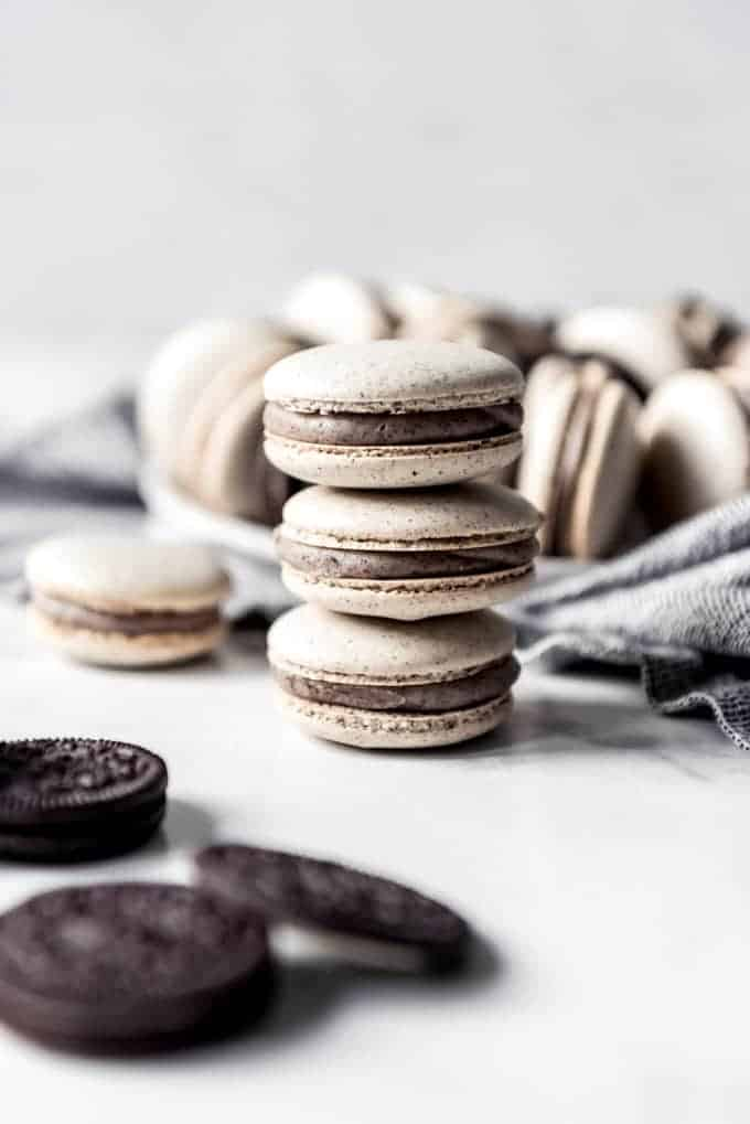 A stack of three cookies and cream macarons.