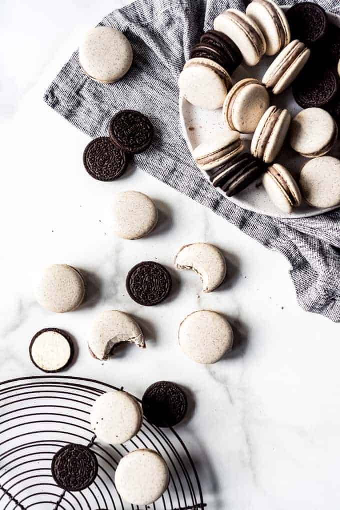 Oreos and cookies & cream macarons with bites taken out of them on a white surface next to a black and white napkin.