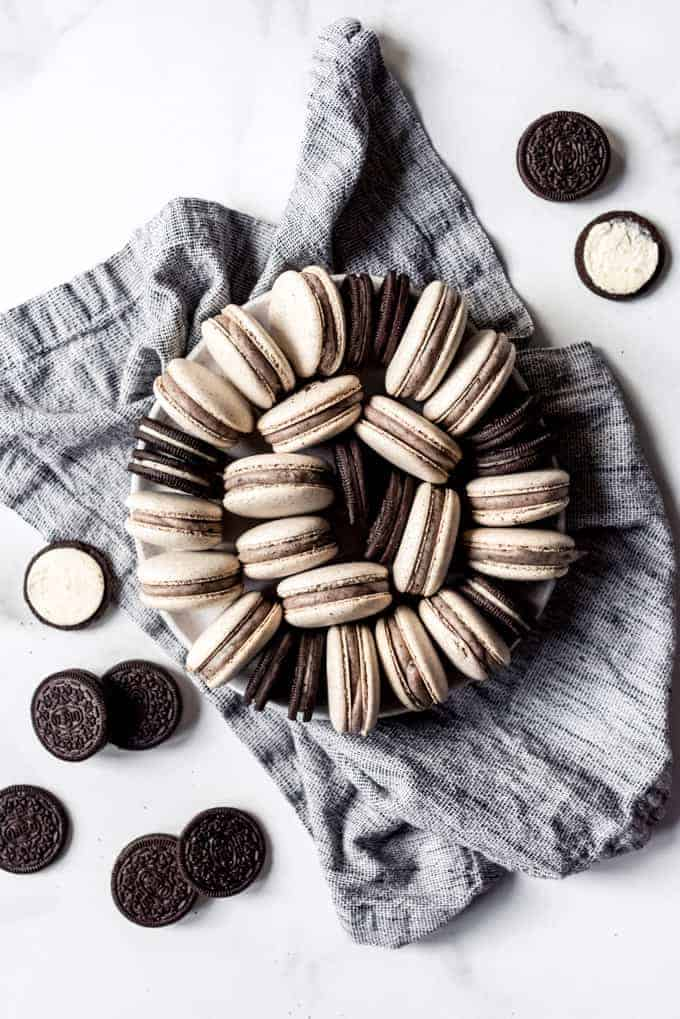 Cookies and cream macarons and Oreos arranged in a circle on a plate set on a black and white napkin.