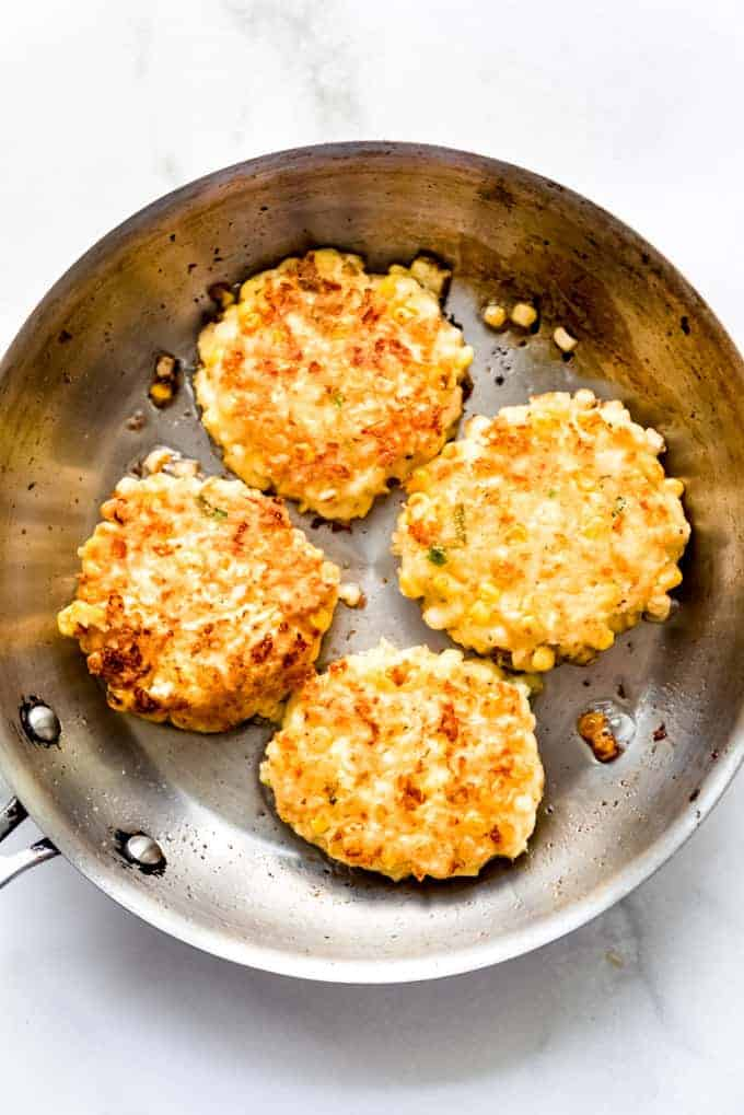 Four lightly browned corn fritters frying in a stainless steel pan with a little oil.