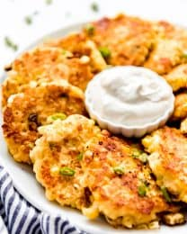 Piles of corn fritters beside a small bowl of sour cream.