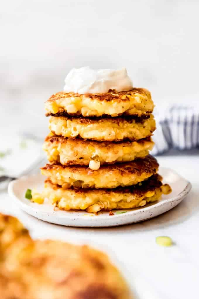 A stack of five corn fritters on a plate with a dollop of sour cream on top.