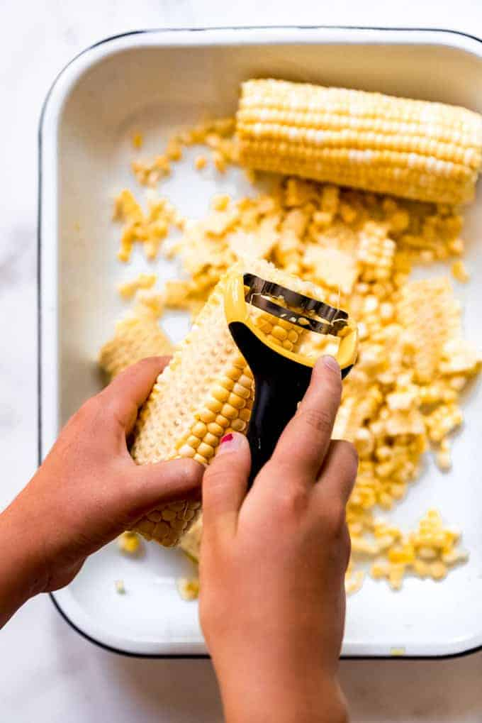 Hands holding a corn cob using a kitchen tool to cut the kernels of corn off the cob into a pan below.