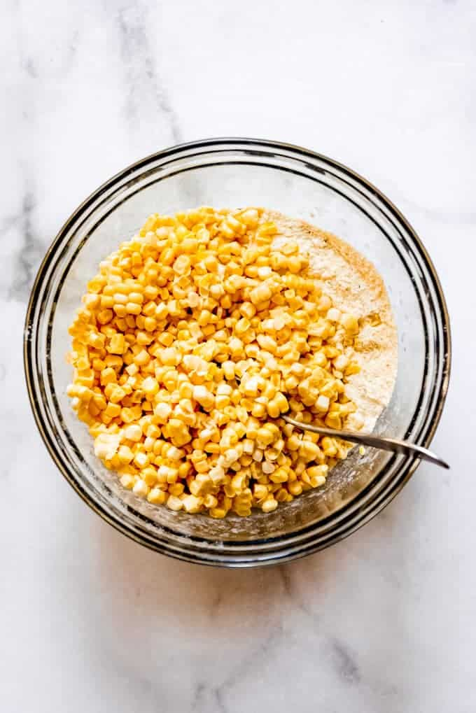 Whole corn kernals added to the flour and cornmeal mixture in a glass bowl