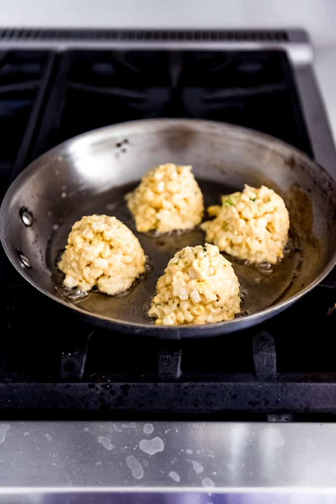 Rounded mounds of corn fritter mixture in a skillet on the stove