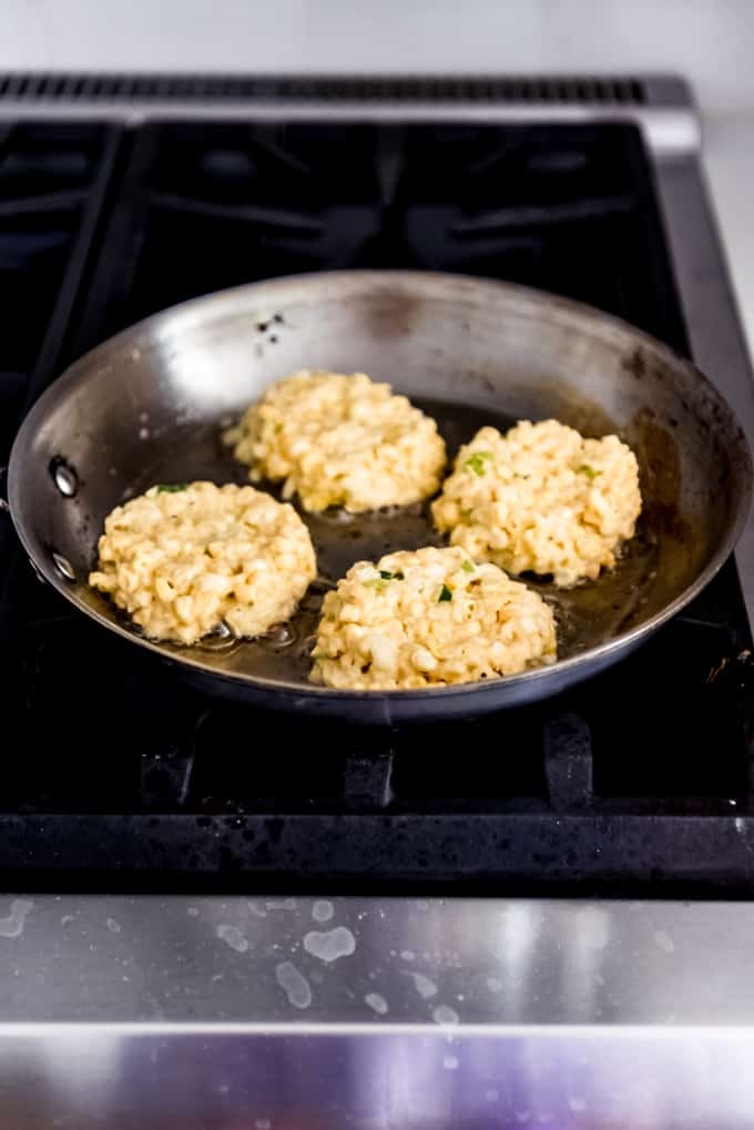 Flattened corn fritter patties on a skillet on the stove