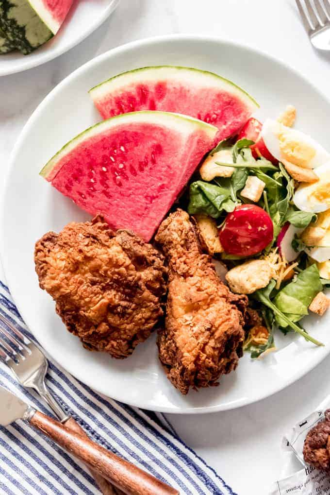Two pieces of fried chicken on a white plate with slices of watermelon and a garden salad.