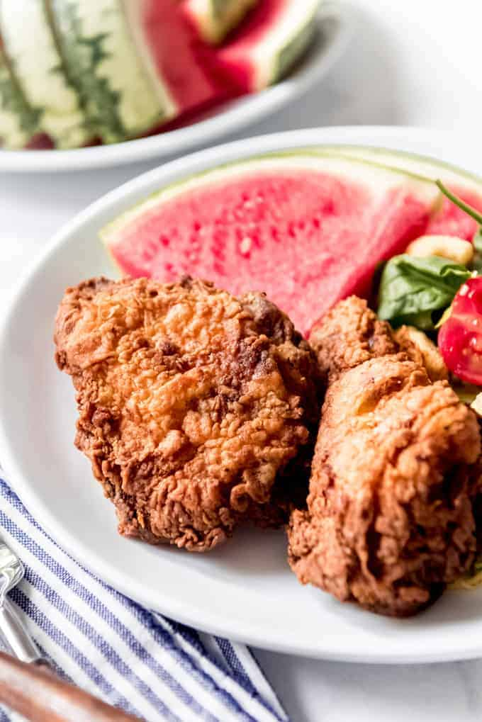 Pieces of fried chicken on a white plate with a slice of watermelon.