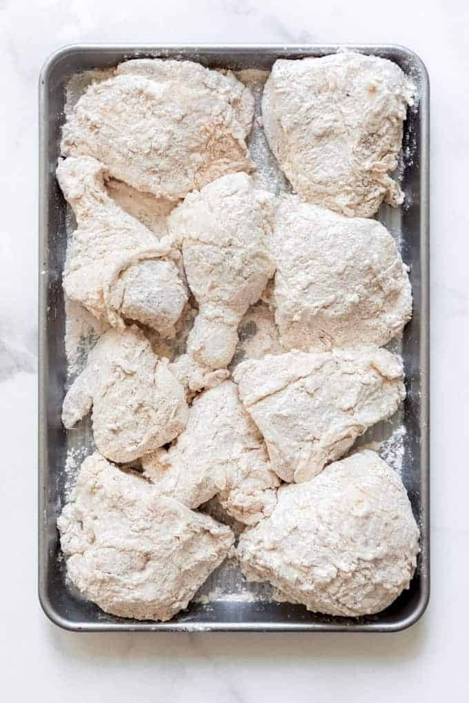 flour coated chicken pieces on a baking sheet
