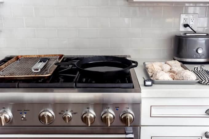 A stove with a baking sheet, wire rack, and thermometer on the left, a cast iron skillet filled with oil in the middle, and a pan of chicken dredged in seasoned flour ready to fry on the right.