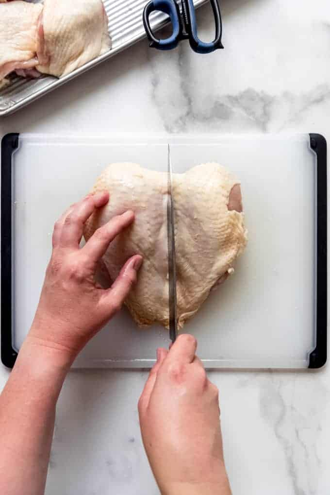 a pair of hands cutting down the middle on a pair of attached chicken breasts