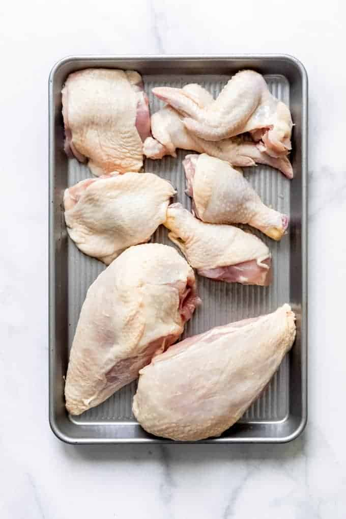 An aerial view of raw cut chicken pieces on a baking sheet