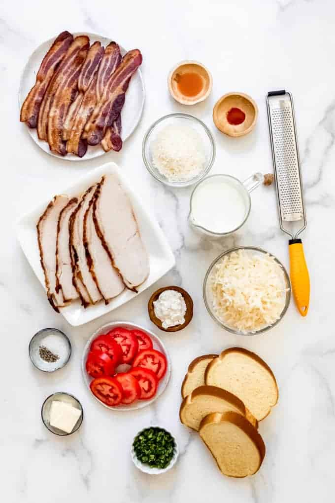 The components for making a hot brown sandwich arrange on a white surface.