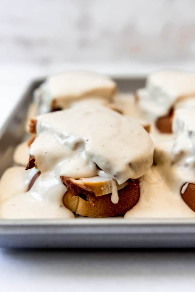 gravy smothered over open faced sandwiches on a baking sheet