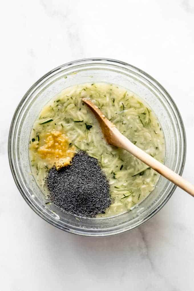 Mixing lemon zest and poppy seeds into a zucchini mixture in a bowl