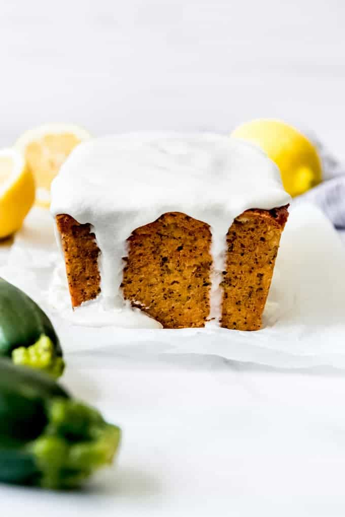 A loaf of lemon poppy seed zucchini bread with lemon icing dripping down the side.